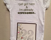 DISCOUNTED -- Nearly Perfect -- #22b, see photos -- I just got here & I'm already awesome.  --- white snapsuit, size 3-6 months.