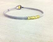 everyday stacking gold nuggets friendship bracelet on adjustable cotton macrame. maggie