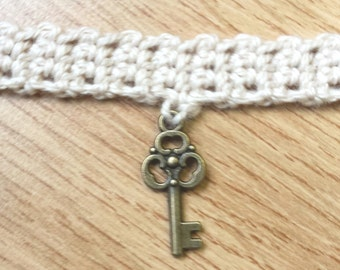 Brass key charm on crochet choker