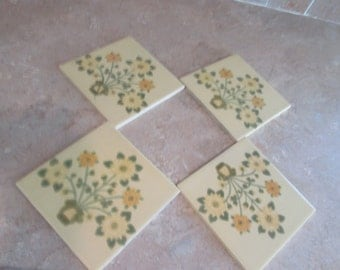Four Vintage ceramic square tiles, pale yellow with green and yellow flowers in a pot. 3.50 each.