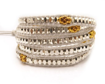 Wrap bracelet with gold skull beads on white leather