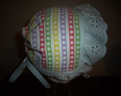 Sweet Easter bonnet with white eyelet ruffle and grosgrain ties and peekaboo back