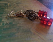 Free shipping in the US ********   Ruby red czech glass rondells on antique brass maze charm.