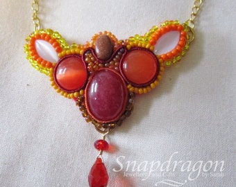 Soutache and bead pendant in vibrant fiery colours. Cherry quartz, goldstone and cats eye cabochons