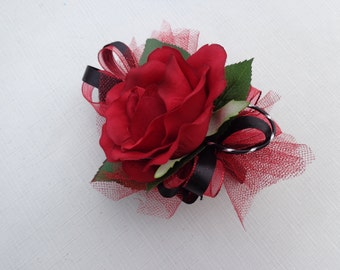 Corsage in red rose trimmed in red and black