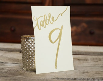 Glitter and Opaque Embossed, Handwritten Calligraphy Table Numbers - Kraft with White or Cream with Gold Glitter Embossing