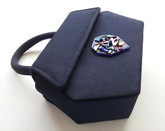 Dark blue evening bag with dichroic tack fused feature.