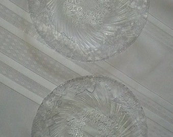 two dessert plates made of glass with fine design on reverse.