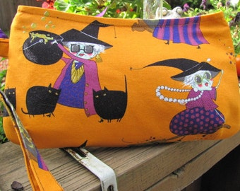 Halloween clutch or wristlet with a silly witch and her black kitties.Lining is bat pattern with orange glitter. Zip close.Handle detaches