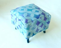 This dollhouse miniature ottoman is aqua and lavender cotton with wooden legs.