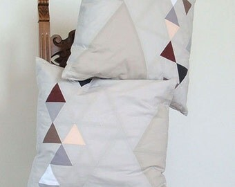 Decorative pillows with triangles graphic, for sofa, patchwork technique, gray and pastels.