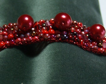 Bright red beaded bracelet with metallic balls.