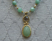 Sea foam green faceted stone hanging from burnt sienna suede.