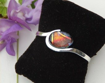 Silver plated over copper cuff bracelet with deep red with stripesdichroic cabochon