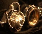 Steampunk goggles in black  leather and silver tone metal with moveable lens and monocle-style eyepiece. - TheTimeCabinet