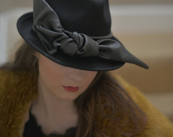 Ladies felt trilby hat with black leather bow detail.