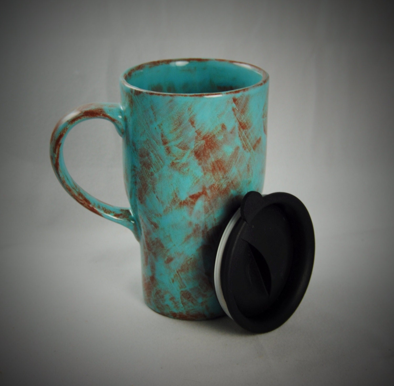 teal and auburn ceramic travel mug with a lid