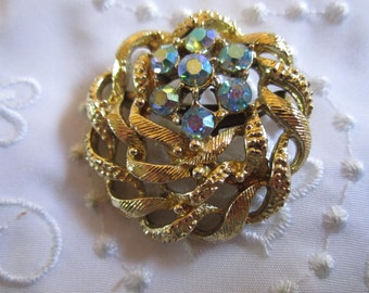 Vintage Intertwined Gold Tone Metal Pattern with Blue Aurora Borealis Rhinestone Flower Brooch
