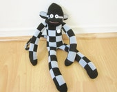 Goofy checkerboard print black and gray white sock monkey doll with vintage button