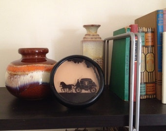SALE C.A. Richards round reverse painted silhouette featuring a stagecoach