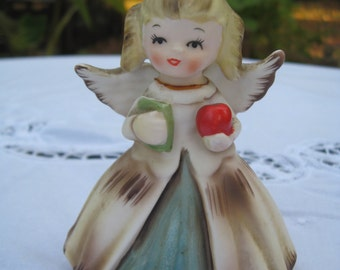 Porcelain Angel with wings and halo brings an apple to teacher