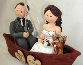Personalised bride and groom on a boat fishing with dog wedding cake topper