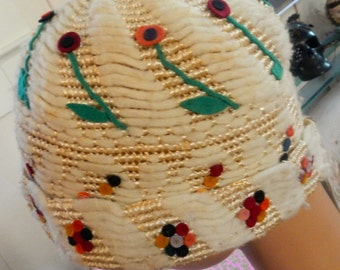 a 20s cloche of straw,chenille,and cut felt,handmade. colors are creme,green,blue,and red