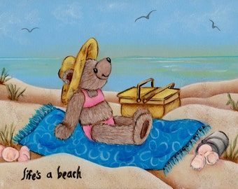 Lifes a beach. Teddy bear soaking up the sun. sand, picnic, basket, shells, water