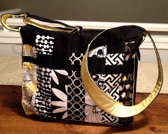 A medium, black, yellow and white upcycled purse with adjustable strap.  Zippered top closure and one zippered pocket inside..