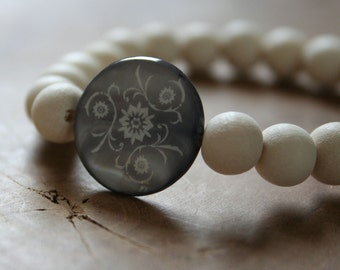 Seaside: an elastic beaded bracelet with white wooden beads and engraved blue-grey mother of pearl