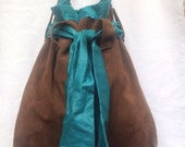 Soft suede shoulder bag with glazed cotton lining and tie.