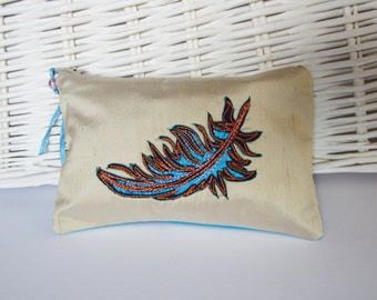 Small zip up silk purse with blue embroidered feather design