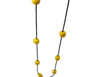 yellow resin bead necklace on black rubber