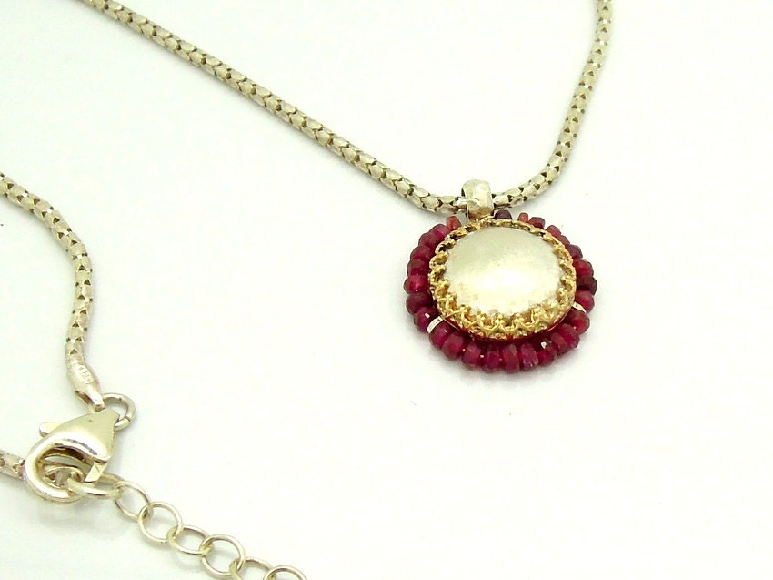 Ruby pendant with a round gold setting on top of textured silver