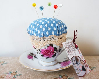 oriental style fabric teacup pincushion with leaf shaped sewing pins.