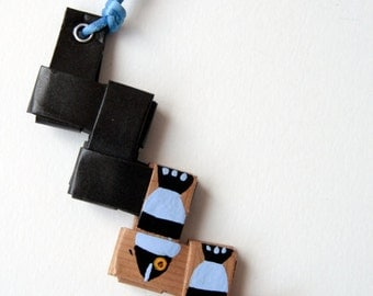 recycled paper necklace decorated with black and blue fishes