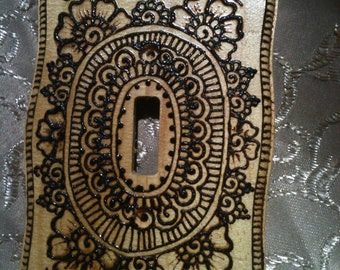 Wooden switchplate decorated with henna