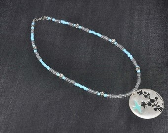 blue & clear beaded necklace with metal pendant