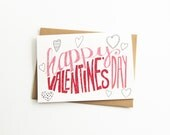 valentine card. happy valentine's day. hand drawn lettering. typography. pink and red. hearts. illustration. recycled paper. blank inside.