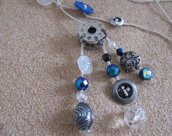 Vintage Buttons and Beads Hang From A Sewing Machine Bobbin