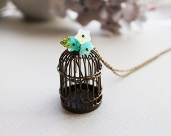 Birdcage Necklace. whimsical bird cage in antique bronze with opal green flowers and sea shell bird