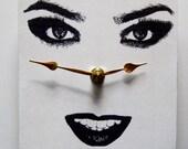 Small square wall clock. Modern face. Woman's face.  Avant garde.