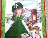 Christmas Card girl in green dress prays for peace