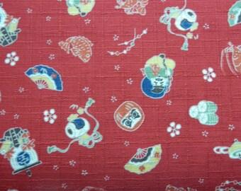 Tissu japonais avec motifs petits personnages daruma, poissons , fond rouge, trame irrégulière - 50 cm