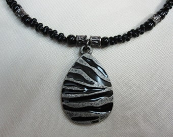 Wow Metal Zebra Print Pendant set on a Black Farfalle Beaded 16 Inch Necklace with Silver Accents and a Sturdy Magnetic Clasp
