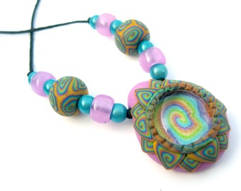 Polymer clay lotus pendant, glow in the dark, millefiori spirals, with glass inclusion, spring colors, with matching beads, rainbow colors