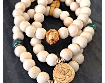 Bone stretch bracelet with double sided vermeil charm. Om charm