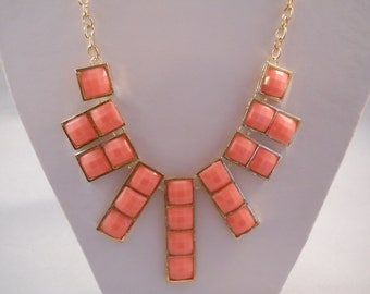 Necklace with Pink/Orange and Gold Tone Pendant Beads on a Gold Tone Chain.