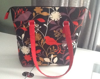 Black and red midnight madness purse has outside pockets with twist lock closure and red cotton lining