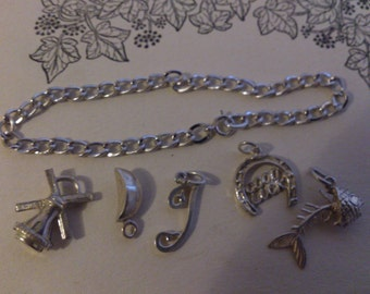 Sterling silver chain bracelet with a selection of vintage silver charms